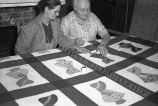 Two women discuss a sunbonnet sue quilt square