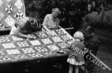 Women and child quilting outside