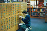 A student looking in the card catalog.